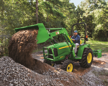 A John Deere 3032E Compact Tractor Dumping Dirt and Gravel into a Pile