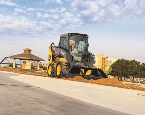 A John Deere 316GR Skid Steer leveling out dirt along a sidewalk