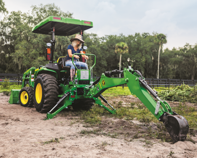 Woman using a 3025E Compact Tractor to dig