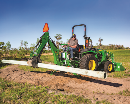 Man using a John Deere 3038E Compact Tractor to position a pipe