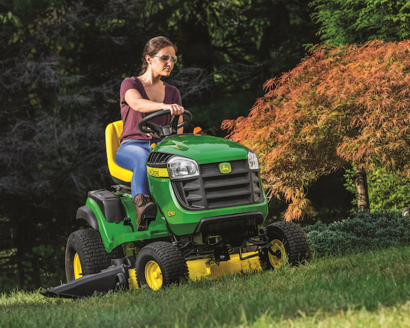 Woman mowing her yard using her John Deere E150 Lawn Tractor
