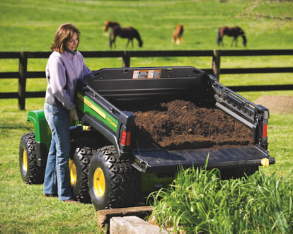 Woman hauling materials in John Deere Gator cargo box