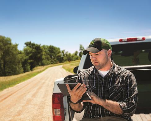 Farmer using his John Deere remote display access to check vital stats