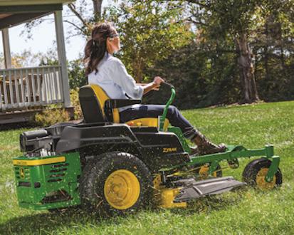 Woman using John Deere Ztrak Mower to cut grass in her yard