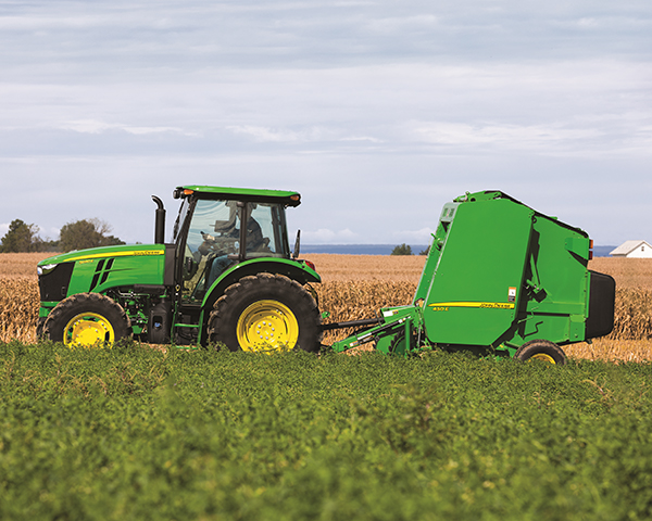 John Deere 450 Baler pulled by utility tractor